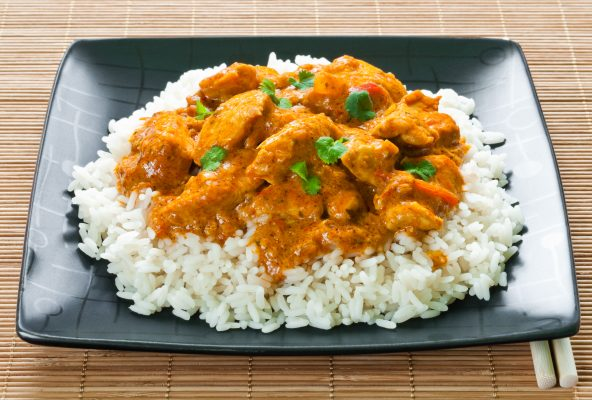 Chicken curry and rice on black plate on bamboo matting